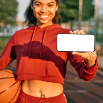 Kobieta trzyma koszykówkę i pusty telefon