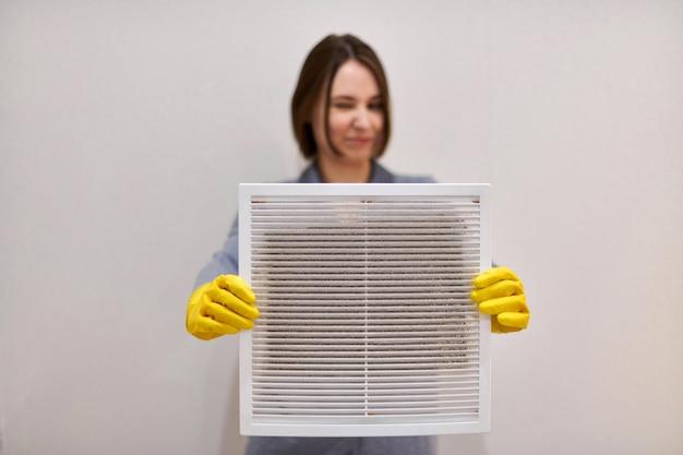 Kobieta trzyma kratkę wentylacyjną z filtrem przeciwpyłowym, aby ją wyczyścić