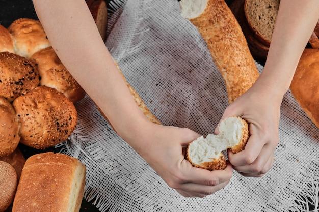 Kobieta trzyma kromki bajgla na ciemnym stole z różnymi chlebami