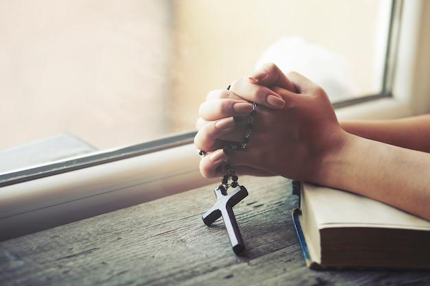 Kobieta trzyma krzyż podczas gdy modli się