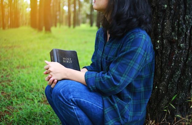 Kobieta trzyma książkę, biblia, natura.