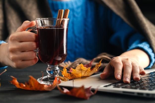 Kobieta trzyma kubek gorącego napoju (herbata jabłkowa, grzane wino). kobiece ręce z kubkiem sezonowego gorącego napoju. domowa gorąca herbata owocowa.