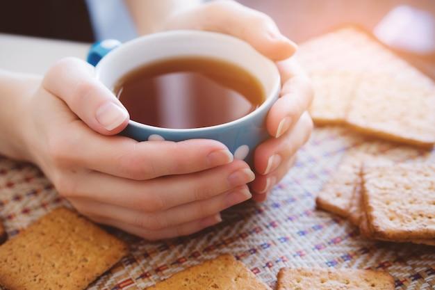 Kobieta trzyma kubek gorącej herbaty lub kawy, leżą obok ciasteczek, zbliżenie