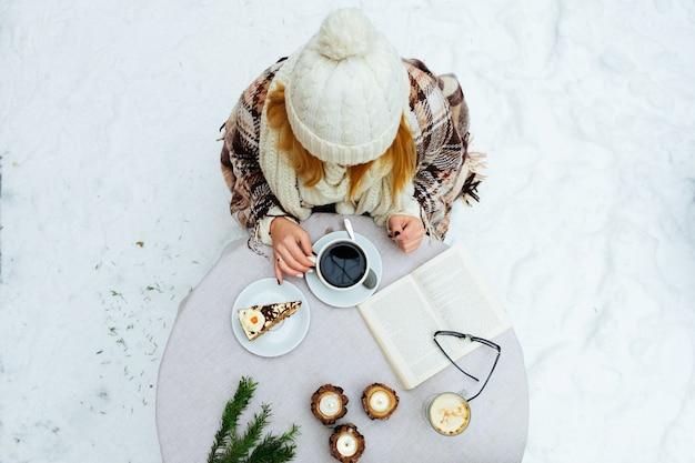 Kobieta trzyma kubek gorącej kawy na rustykalnym drewnianym stole, zbliżenie zdjęcie rąk w ciepły sweter z kubkiem, zimowy poranek koncepcja, widok z góry