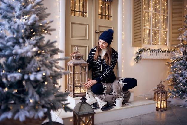 Kobieta trzyma kubek gorącej kawy w zimie w pobliżu okna w domu z na zewnątrz w tle.