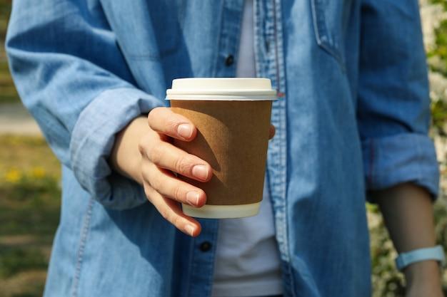 Kobieta trzyma kubek kawy puste papieru. kwitnące wiosną
