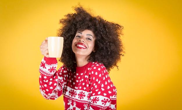 Kobieta trzyma kubek na boże narodzenie, żółte tło