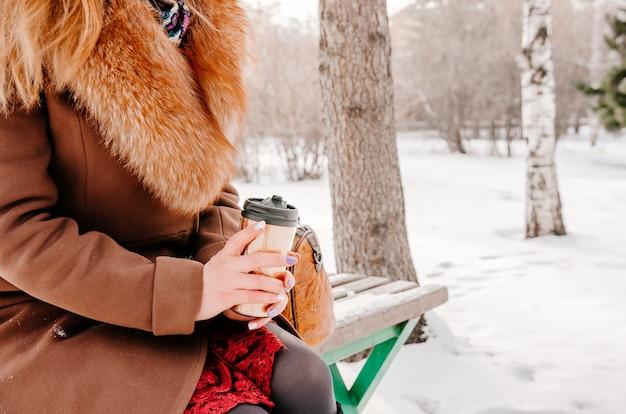 Kobieta trzyma kubek termiczny. koncepcja stylu życia