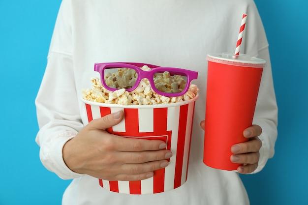 Kobieta trzyma kubek z popcornem i okularami 3d i pije na niebieskim tle.