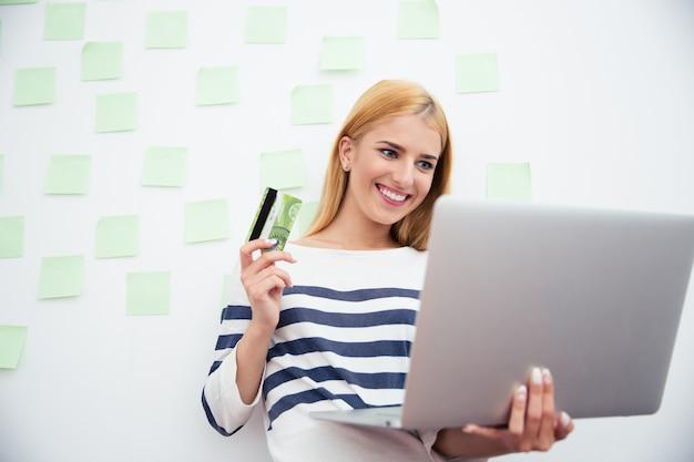 Kobieta trzyma laptop i kartę bankową