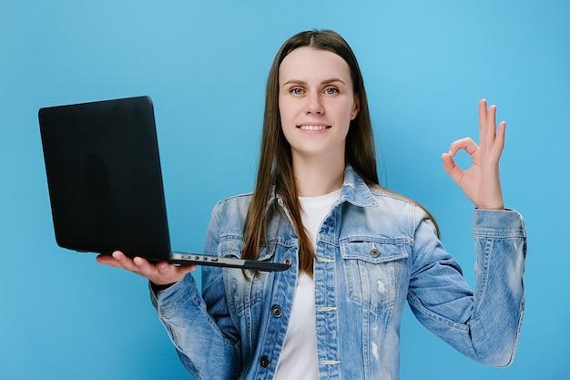 Kobieta trzyma laptopa pokazując ok gest