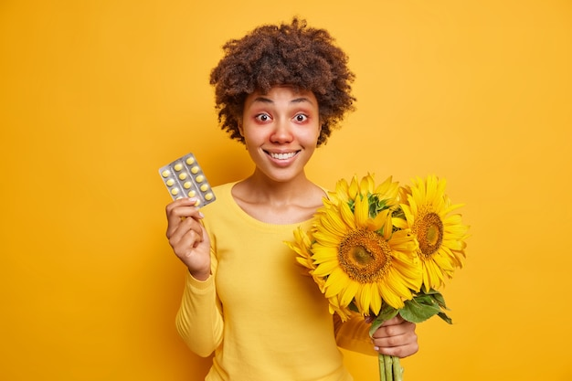 Kobieta trzyma leki i bukiet słoneczników cierpi na alergiczny nieżyt nosa i zaczerwienienie oczu ubrana niedbale na żywym żółtym kolorze