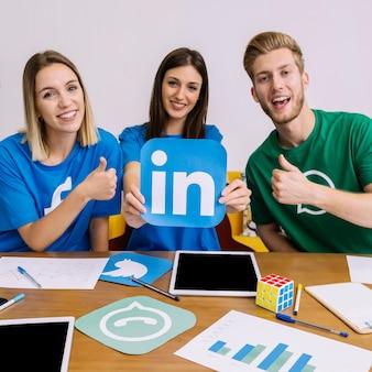 Kobieta trzyma linkedin logo z jego przyjaciółmi pokazuje thumbup znaka