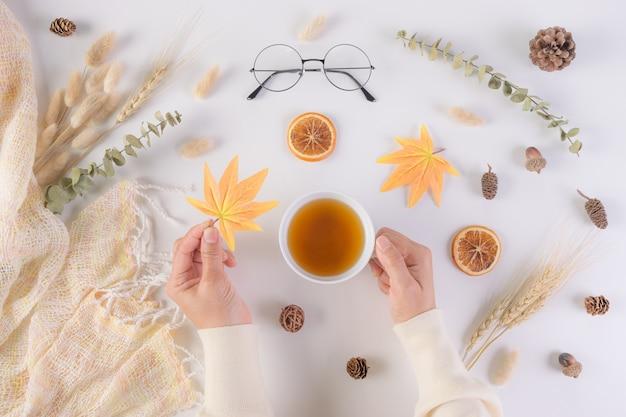 Kobieta trzyma liść klonu i filiżankę herbaty na tle jesieni.
