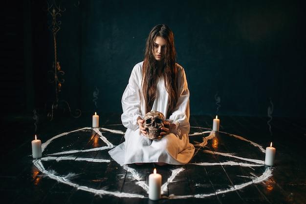Kobieta trzyma ludzką czaszkę w ręku, mroczna magia, wiedźma