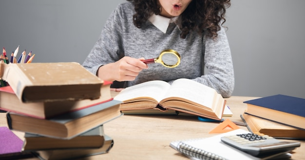 Kobieta trzyma lupę i czyta książkę