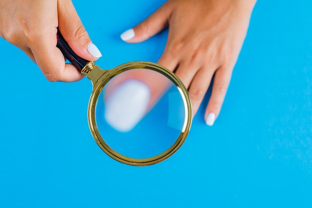 Kobieta trzyma lupę nad paznokciem