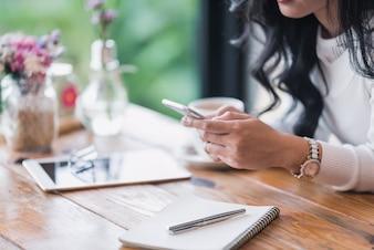 Kobieta trzyma mądrze telefon z filiżanką i używa