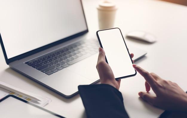 Kobieta trzyma mądrze telefon, laptop i pastylkę na stole, wyśmiewa pusty ekran.
