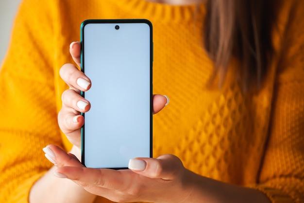 Kobieta trzyma makietę ekranu telefonu komórkowego w rękach w pomarańczowym swetrze