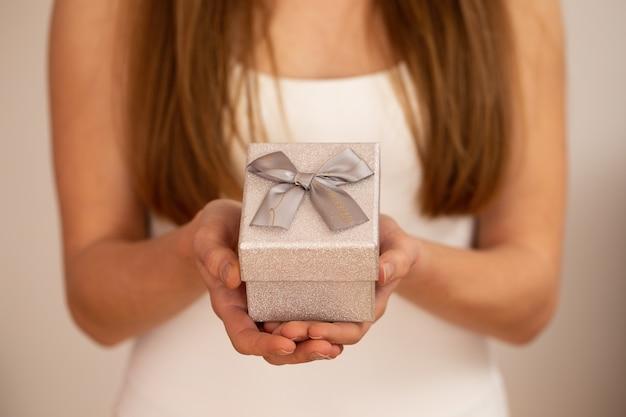 Kobieta trzyma małe srebrne pudełko ze wstążką na białym tle