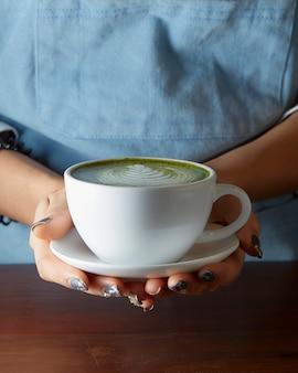 Kobieta trzyma matcha zielonej herbaty latte