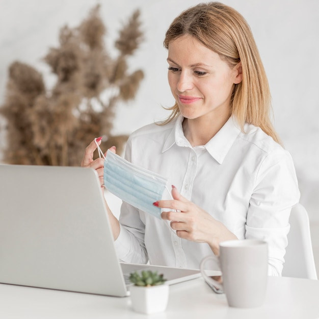 Kobieta trzyma medyczną maskę przed jej laptop kamerą