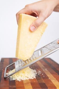 Kobieta trzyma metal tarka i tarcie sera