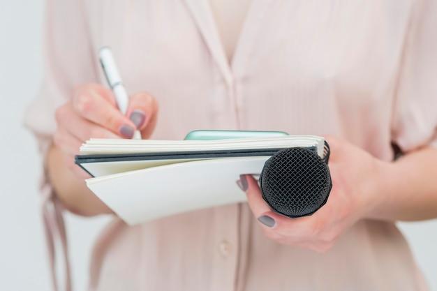 Kobieta trzyma mikrofon i pisze notatki