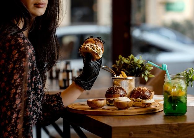 Kobieta trzyma mini burger na sobie czarne rękawiczki