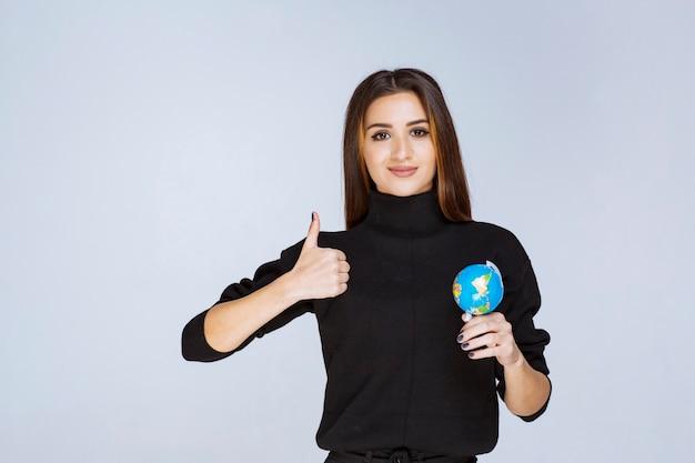 Kobieta trzyma mini globus i pokazuje kciuk w górę.