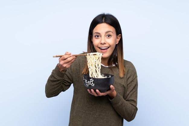 Kobieta trzyma miskę makaronu pałeczkami i je