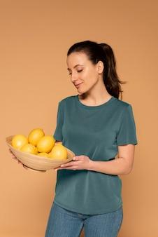 Kobieta trzyma miskę z cytrynami