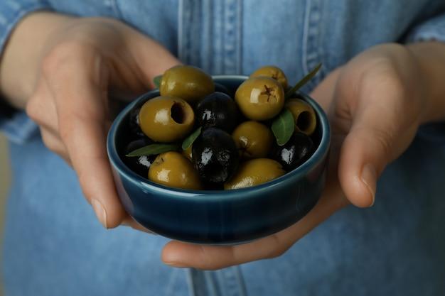 Kobieta trzyma miskę z oliwkami, z bliska