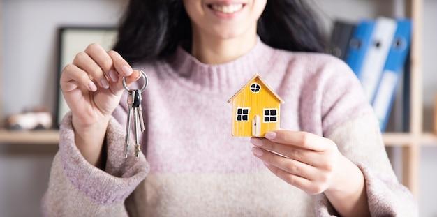 Kobieta trzyma model domu i klucz, koncepcja budynku