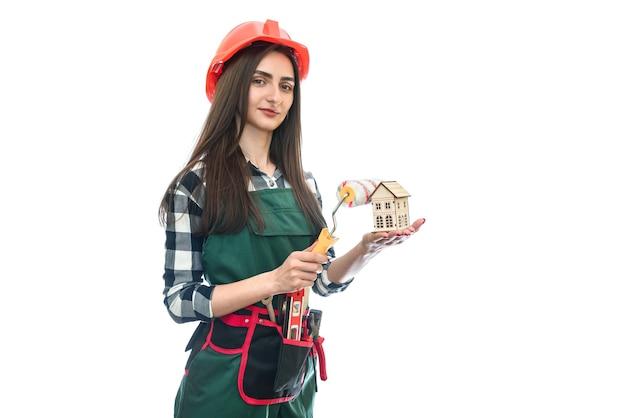 Kobieta trzyma model domu i rolki na białym tle