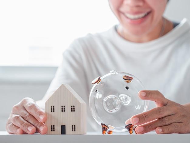 Kobieta trzyma model domu i skarbonkę na białym stole i twarz uśmiech kobiety tle
