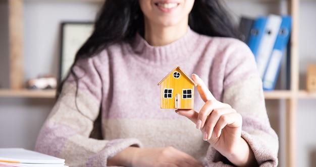 Kobieta Trzyma Model Domu W Biurze, Koncepcja Budynku Premium Zdjęcia