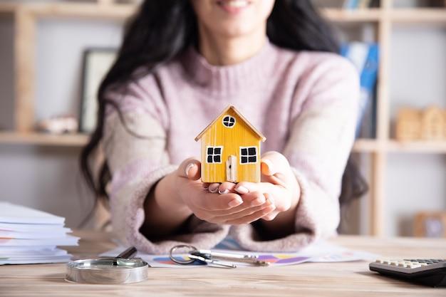 Kobieta trzyma model domu w biurze, koncepcja budynku