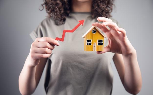 Kobieta trzyma model domu ze strzałką