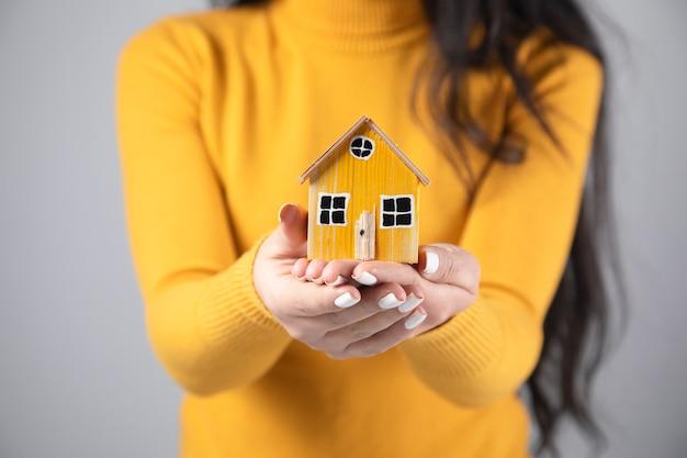 Kobieta trzyma model żółty drewniany dom