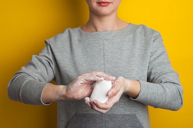 Kobieta trzyma mydło w jej rękach i pokazuje. dłonie i palce w mydlanej pianie rozciągają mydło do przodu. dezynfekcja rąk w walce z koronawirusem.