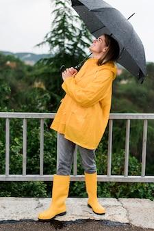 Kobieta trzyma na zewnątrz otwarty czarny parasol