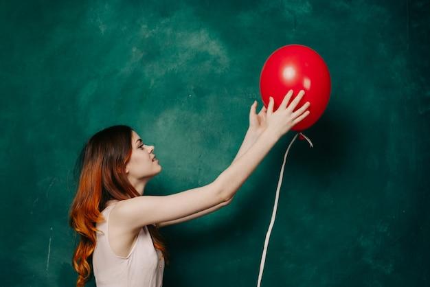 Kobieta trzyma nadmuchiwaną czerwoną piłkę w ręku na zielonym tle prezenty świąteczne