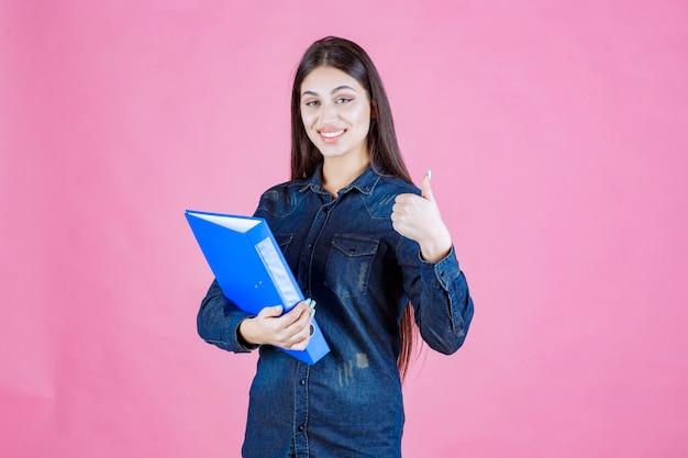 Kobieta trzyma niebieski folder i robi dobry znak