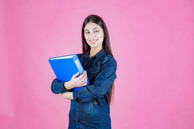 Kobieta trzyma niebieski folder z pewnością siebie