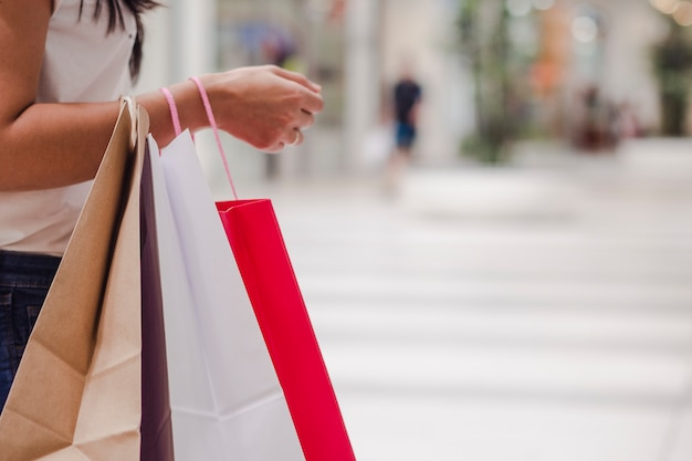 Kobieta trzyma niektóre torba na zakupy podczas gdy stojący w centrum handlowym. obraz poziomy.