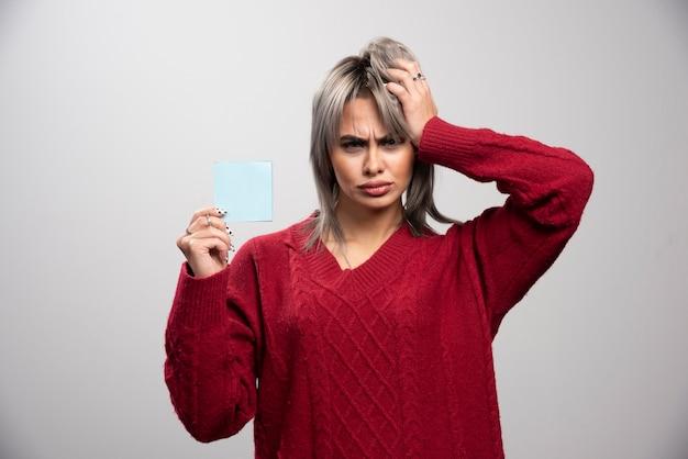 Kobieta trzyma notatnik i myśli o pracy.