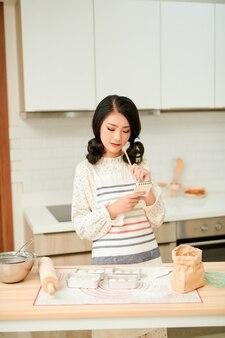 Kobieta trzyma notatnik podczas przygotowywania domowego ciasta przy stole