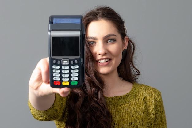 Kobieta trzyma nowoczesny bankowy terminal płatniczy do przetwarzania płatności kartą kredytową, koncepcja stylu życia